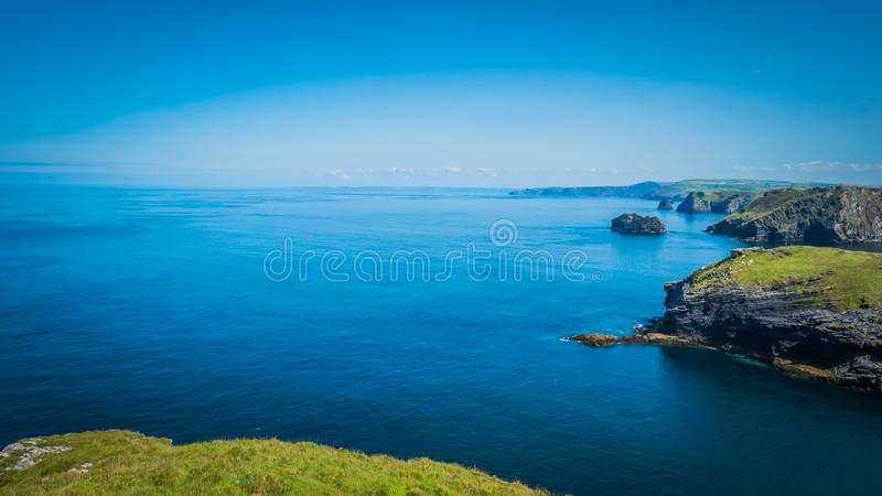 Скалистые ландшафты и скалы на замке Tintagel в Корнуолле, Англии с береговой линией Атлантического океана стоковая фотография rf