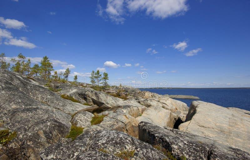 Скалистый берег гранитного острова в солнечном свете стоковые изображения rf