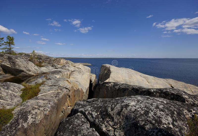 Скалистый берег гранитного острова в солнечном свете стоковое изображение