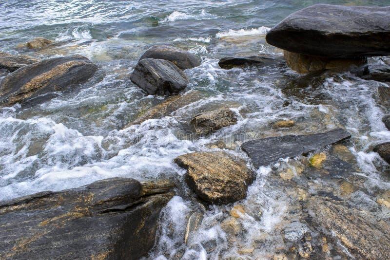 Скалистый берег на белой предпосылке стоковые фотографии rf