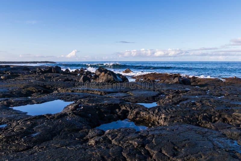 Скалистый вулканический бечевник в Гаваи Малая вода; бассейны воды в полостях утеса Волны, небо океана голубое и облака в предпос стоковые фото