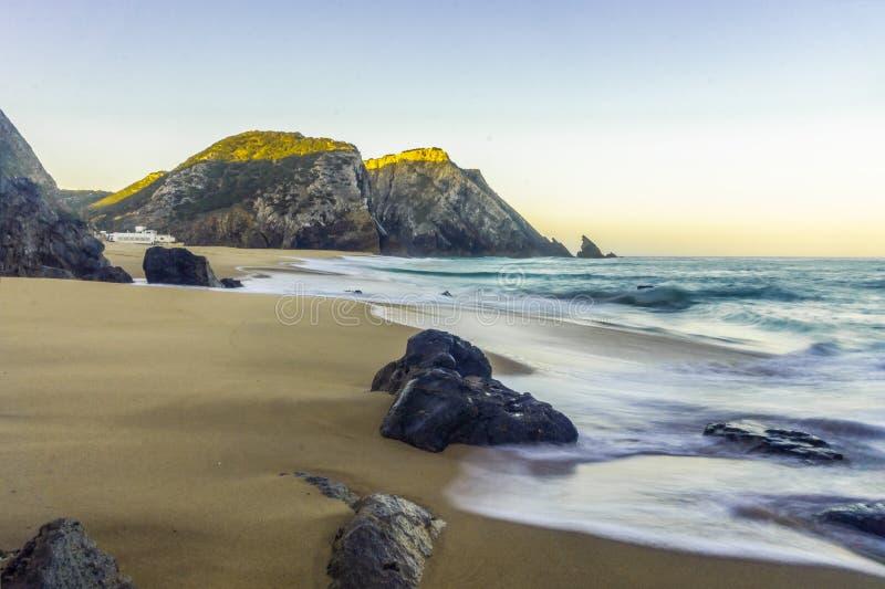 Скалистый и песчаный пляж на восходе солнца, Португалия стоковые изображения
