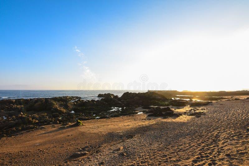 Скалистый и песчаный пляж на заходе солнца, с голубым небом, в Порту, Португалия стоковые изображения rf