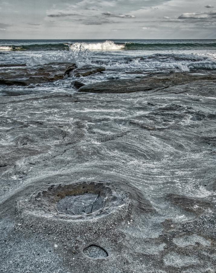 Скалистый пляж с кратером луны как поверхность, волны и облака стоковая фотография