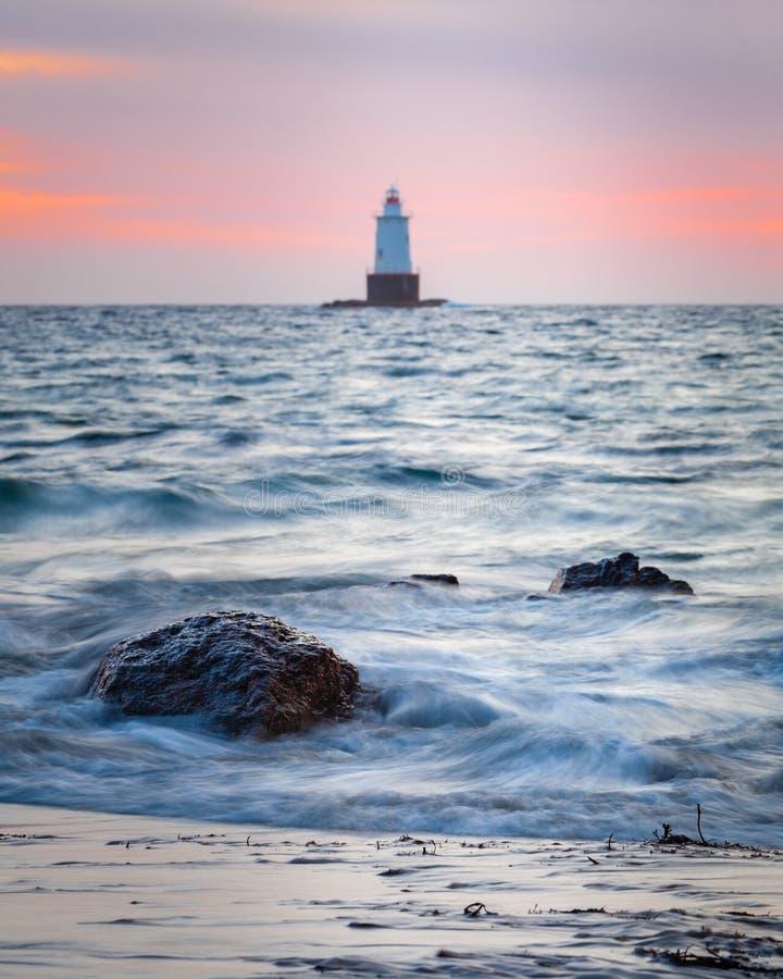 Скалистый прибрежный Seascape маяка на заходе солнца стоковые изображения
