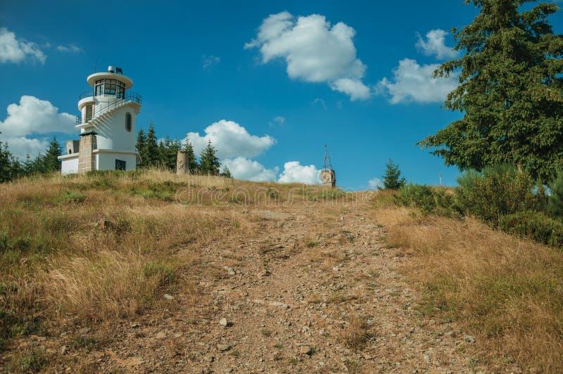 Скалистый след идя к маяку поверх холма стоковое изображение