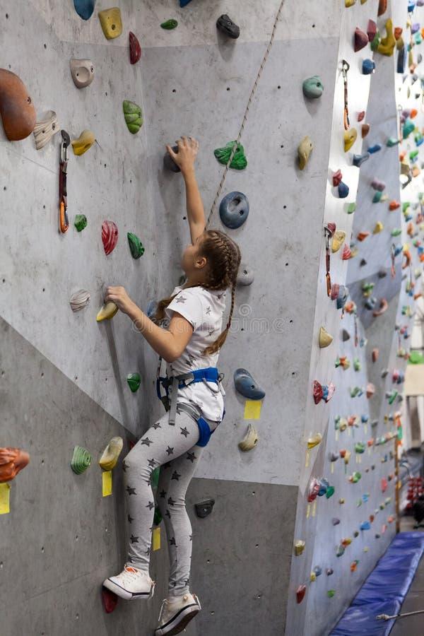 Скалолазание в крытом спортзале, девушке имеет тренировки альпинизма стоковая фотография rf