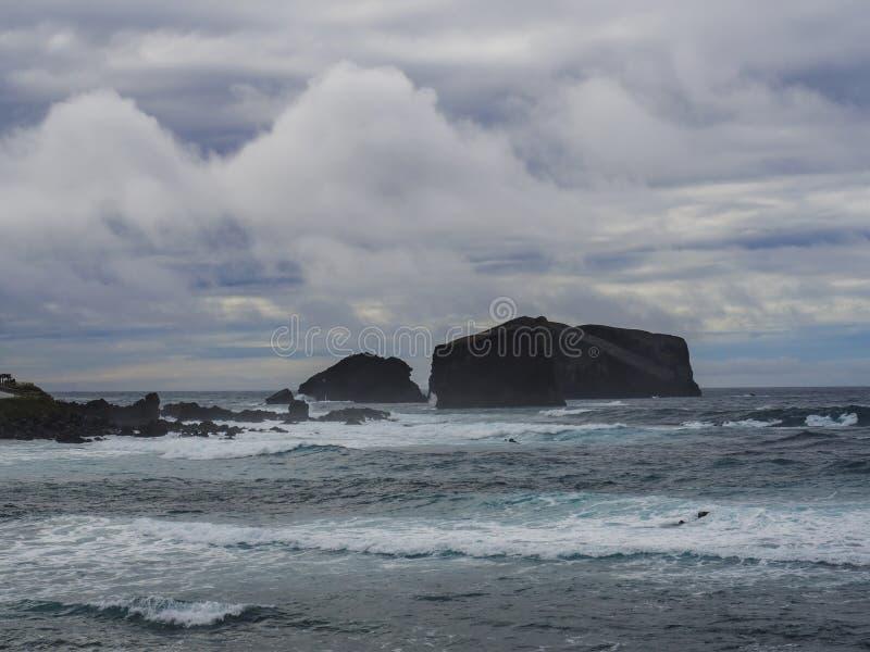 Скалы вулканической породы и каменное образование на деревне Mosteiros, волнах бурного моря Остров Мигеля Sao, Азорские островы,  стоковое фото