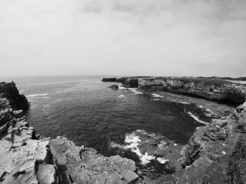 Скалы камней формируя с океаном и небом с некоторыми облаками показывая силу бога с природой стоковое фото rf