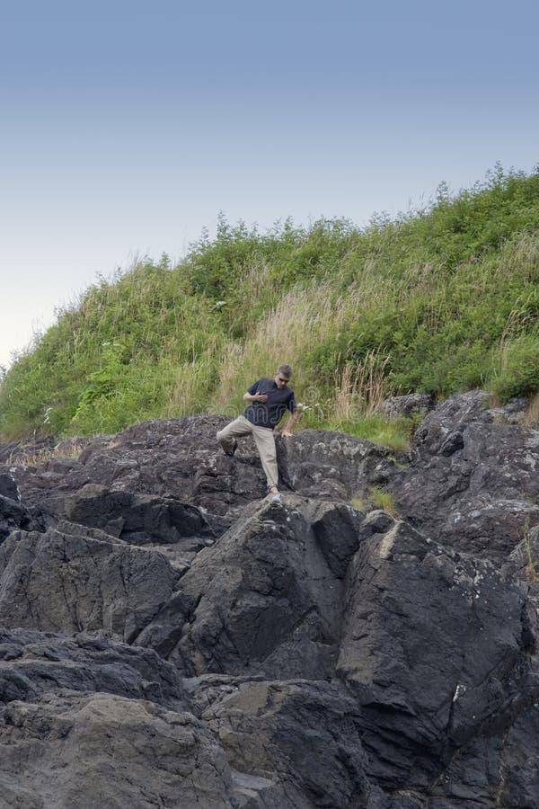 скалы пляжа взбираясь длинний человек возмужалый стоковая фотография rf