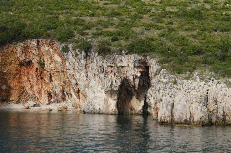 Скалы с малыми пещерами на побережье в Хорватии стоковые фотографии rf