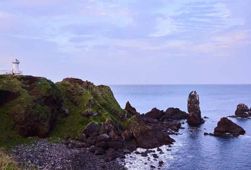Скалы Supjikoji в острове Jeju, Южной Корее с белым маяком и свече сформировали утес в море стоковое фото