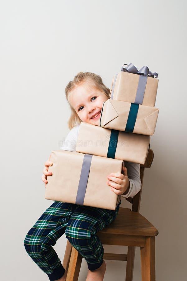 Скандинавская концепция рождества и Нового Года минимализма с ребенк - маленькой девочкой со стогом подарочной коробки на стуле в стоковая фотография