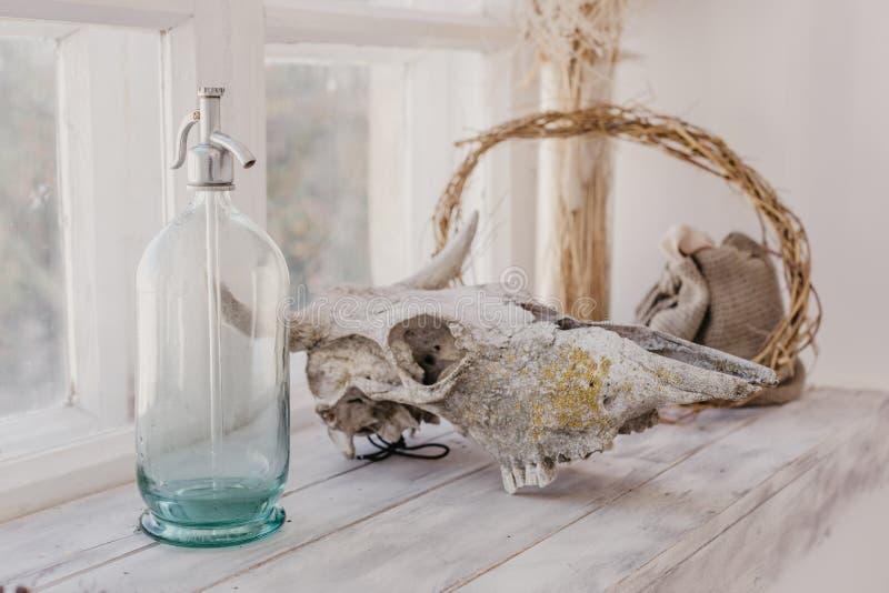 Скандинавские детали стиля около окна, стеклянного сифона, животного черепа стоковые фотографии rf