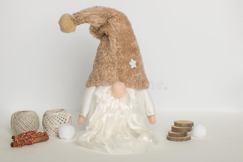 Скандинавский гном в белых одеждах и бежевой шляпе с шерстяными шариками, циннамоном и кусками дерева на белой предпосылке стоковые фото