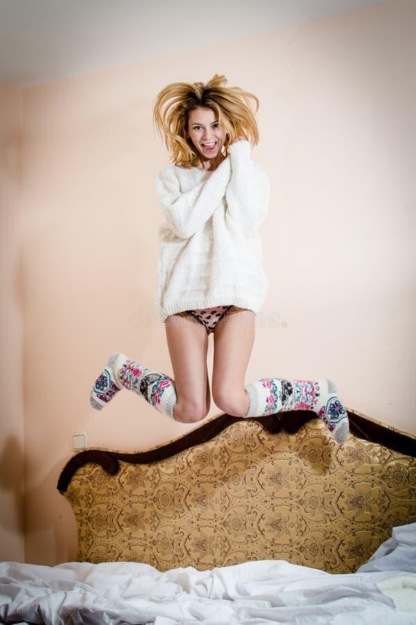 скача высокая привлекательная красивая молодая белокурая женщина имея потеху сексуальную на кресле, счастливый усмехаться стоковое изображение