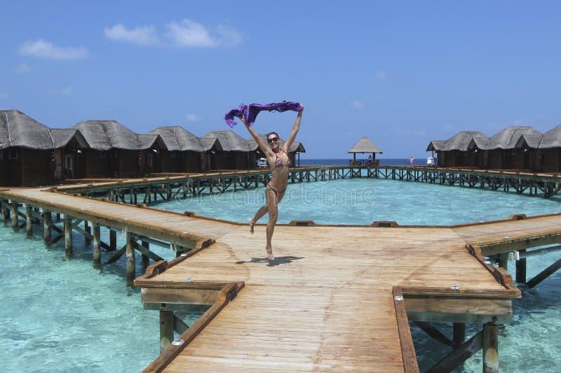 Скача девушка в курорте Мальдивов стоковая фотография rf