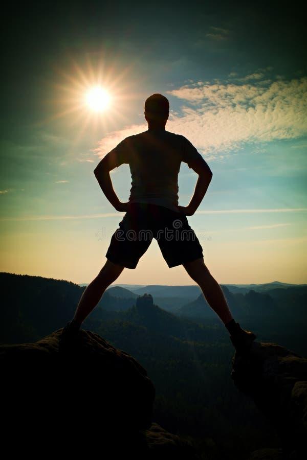 Скача hiker в черных брюках празднует триумф между 2 скалистыми пиками Чудесный солнечный рассвет стоковые фотографии rf
