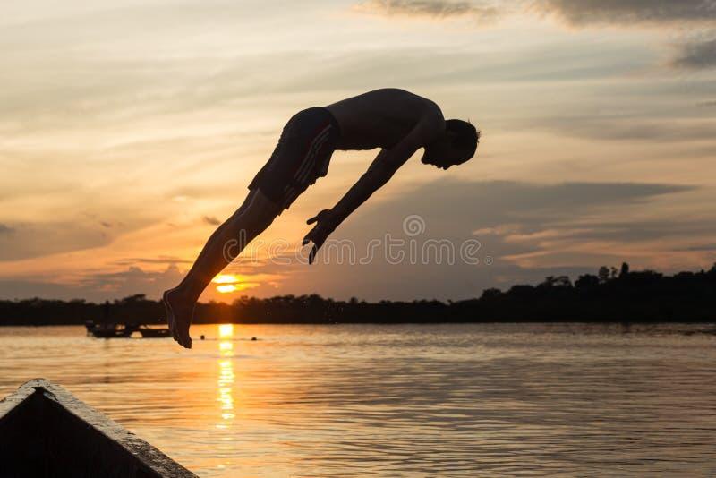 Скачка воды против захода солнца стоковое изображение rf