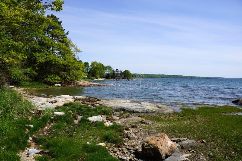 Скалистая береговая линия с пристанью в расстоянии и зеленые деревья на Littlej стоковые изображения rf