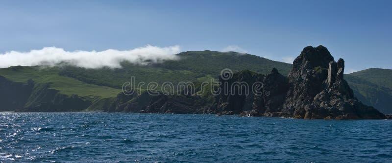 Скалистое побережье острова, который покрывает туман стоковые изображения