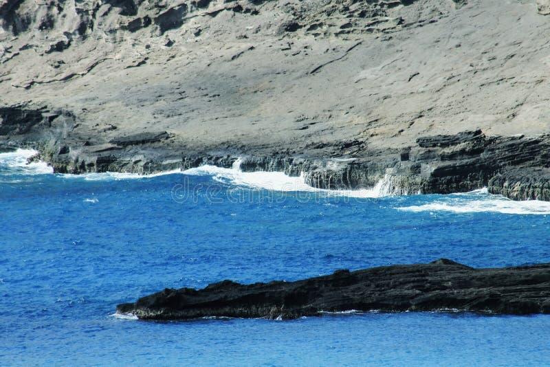 Скалистый выход на поверхность в гаваиских открытых морях стоковое фото rf