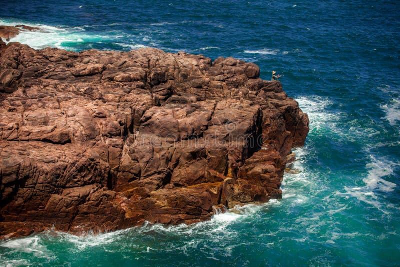 Скалистый выход на поверхность в море стоковые изображения