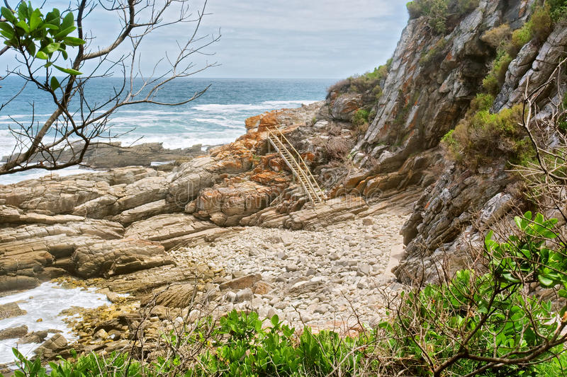 Скалистый пляж и лестница стоковое фото