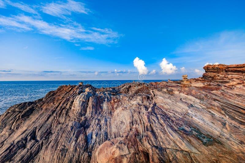 Скалистый seashore в восходе солнца утра с яркими голубым небом и облаками стоковая фотография rf