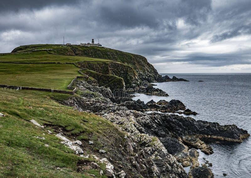 Скалы и маяк, голова Sumburgh, материк Shetland стоковые фото