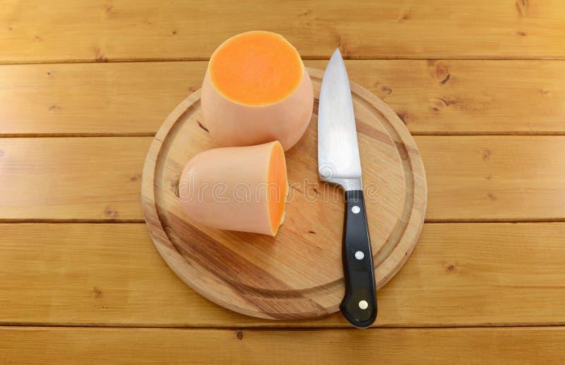 Сквош Butternut отрезал в половине с ножом на деревянной доске стоковая фотография rf