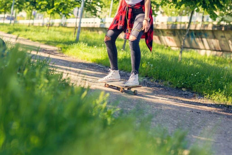 Скейтбордист женщины - ноги skateboarding в парке стоковые фотографии rf