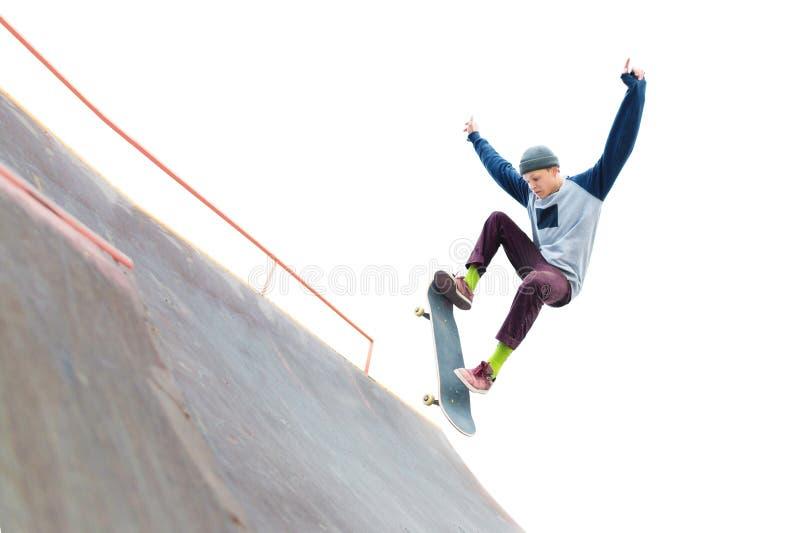 Скейтбордист подростка в крышке делает фокус с скачкой на пандусе в skatepark Изолированные конькобежец и пандус дальше стоковая фотография