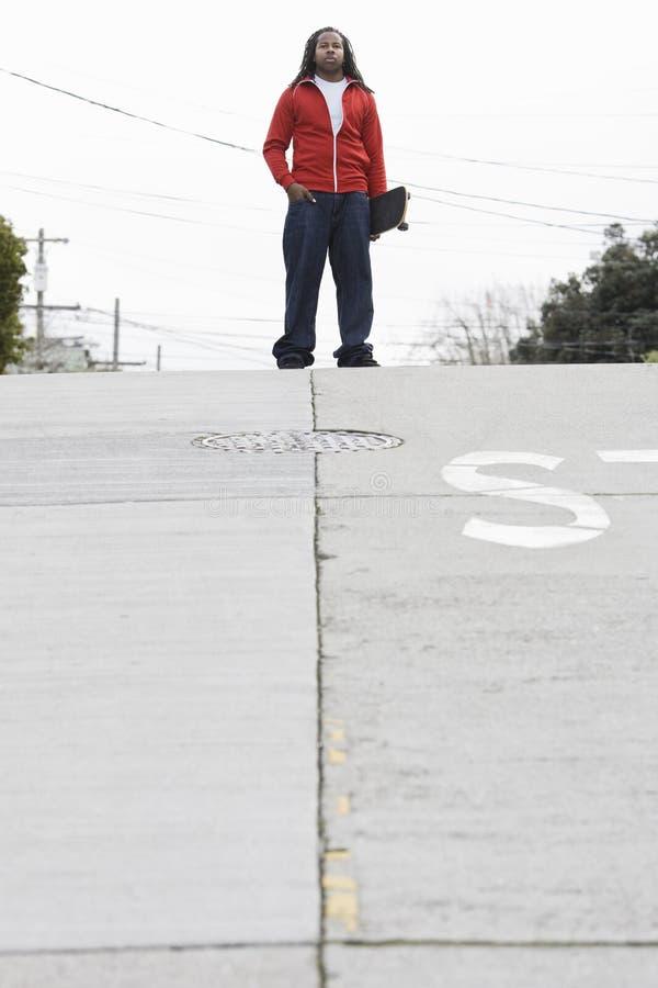 скейтборд мальчика стоя предназначен для подростков стоковые изображения rf