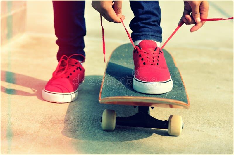 Скейтбордист женщины связывая шнурок стоковая фотография rf