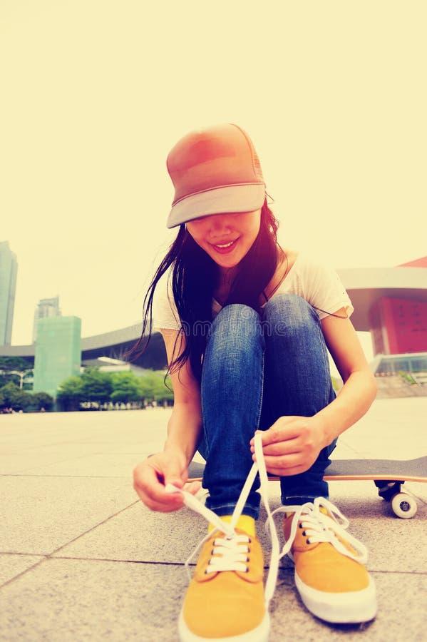 Скейтбордист молодой женщины связывая шнурок стоковые фото