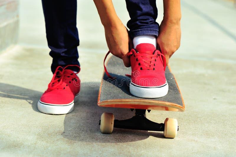 Скейтбордист молодой женщины связывая шнурок стоковые фотографии rf