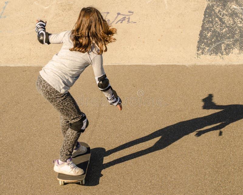 Скейтборд катания маленькой девочки стоковые фотографии rf