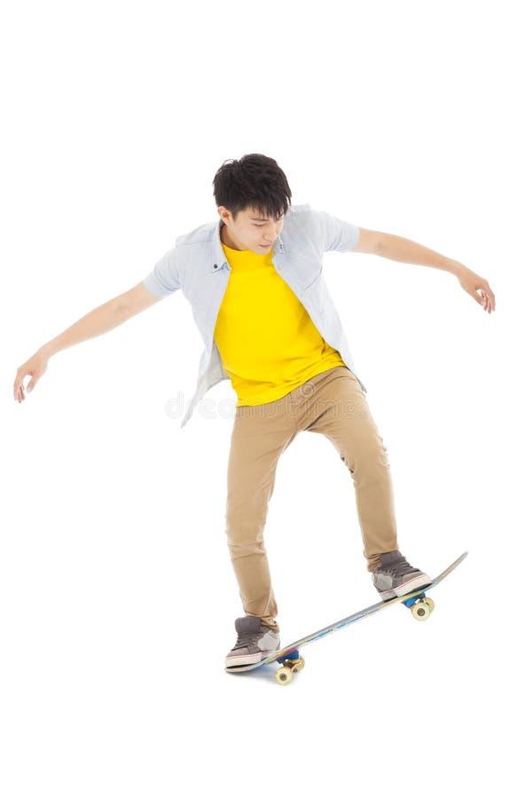 Скейтборд молодого человека, который нужно поскакать изолировал на белизне стоковая фотография