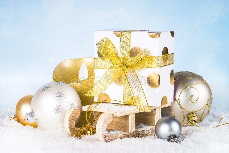 Скелетон с присутствующими украшениями коробки, серебряных и золотых в снеге стоковое фото rf