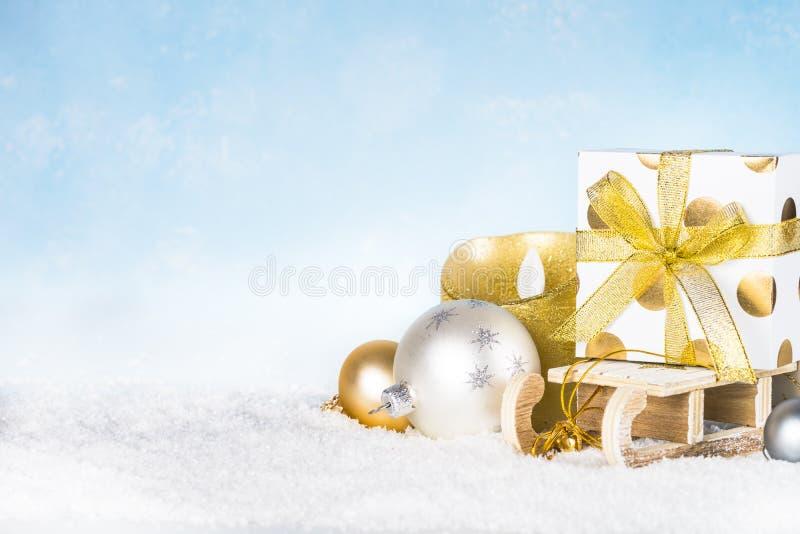 Скелетон с присутствующими украшениями коробки, серебряных и золотых в снеге стоковая фотография