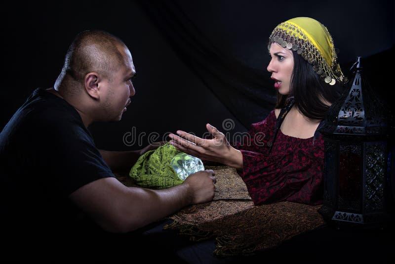 Скептичный человек с рассказчиком удачи мошенника стоковое изображение
