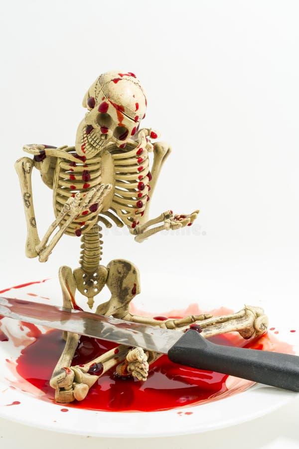 Скелет натюрморта в крови с ножом на белой предпосылке стоковое изображение rf