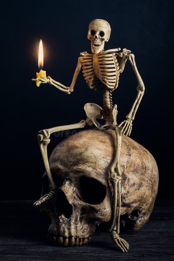 Скелет сидя на большом черепе стоковое фото rf