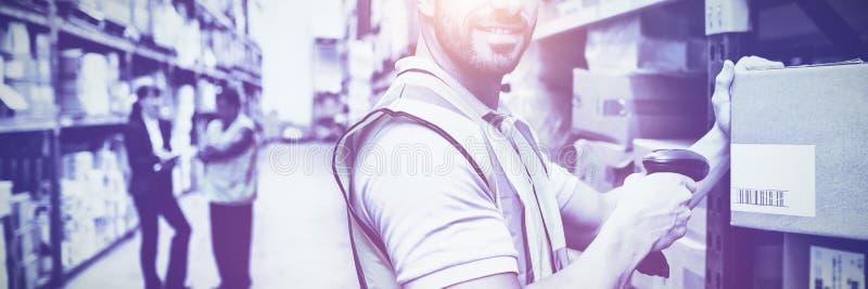 Складируйте коробка скеннирования работника пока усмехающся на камере стоковая фотография rf
