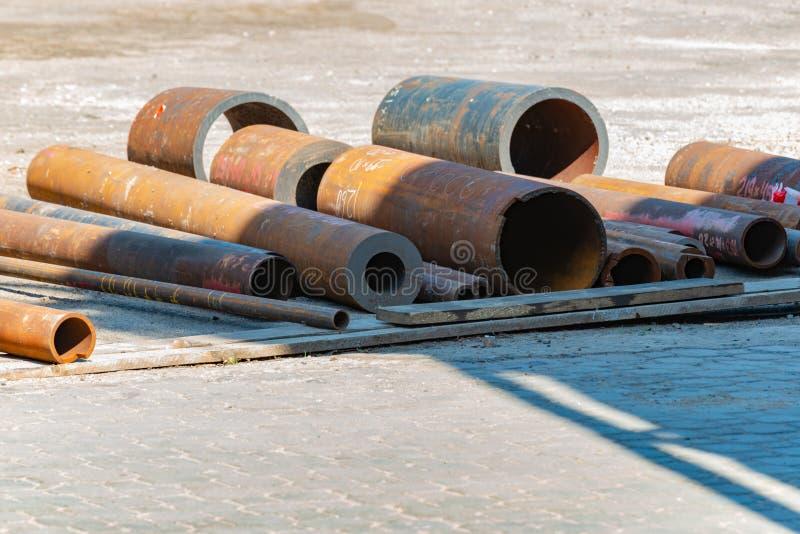 Склад металла на открытом воздухе, трубы и бары ржавеют в улице стоковые фото