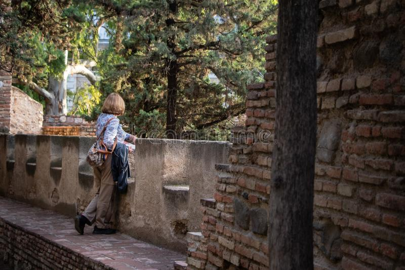 Склонность женщины на балконе смотря на сосны стоковое фото