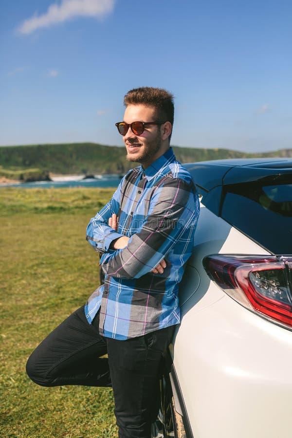 Склонность молодого человека на его автомобиле стоковое фото rf
