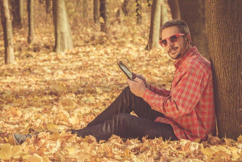 Склонность молодого человека против дерева и удерживание tablet прибор стоковое изображение rf