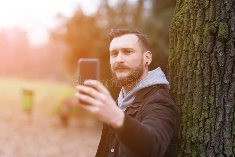 Склонность человека битника против дерева и принимать selfie стоковые фотографии rf